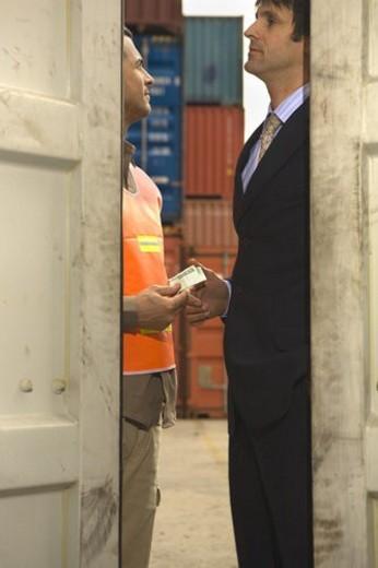 Businessman bribing a dock worker : Stock Photo