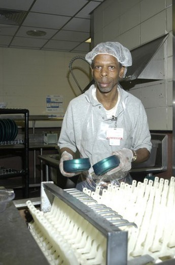 Man with disabilities in a commercial kitchen washing dishes. : Stock Photo