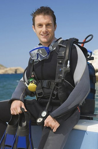 Stock Photo: 4029R-88323 A male scuba diver sitting on a boat