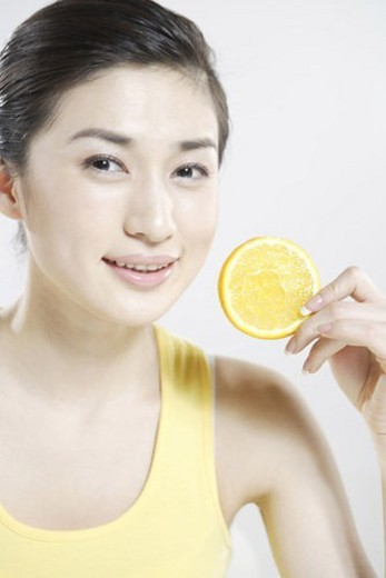 Young woman holding a lemon slice : Stock Photo