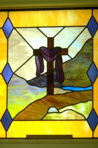 Purple cloth draped on cross on stained glass church window : Stock Photo