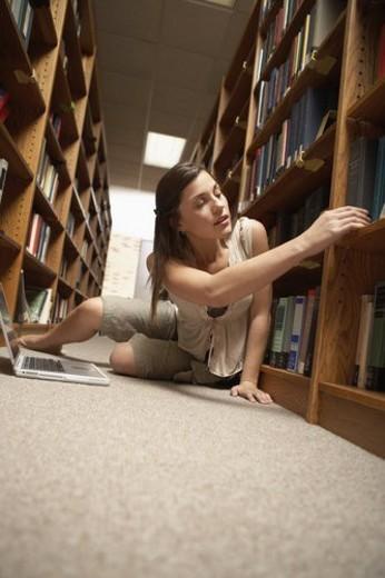 Teenage girl studying on library floor : Stock Photo