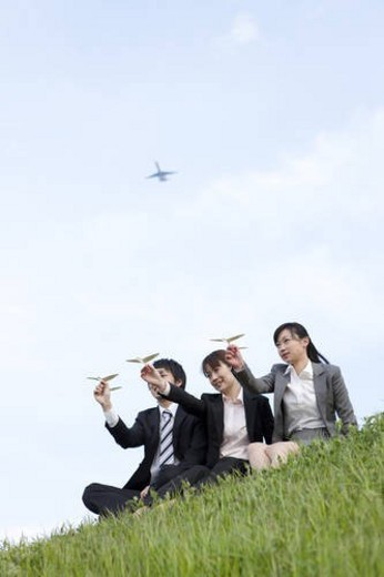 Businessman and businesswomen playing with paper planes : Stock Photo