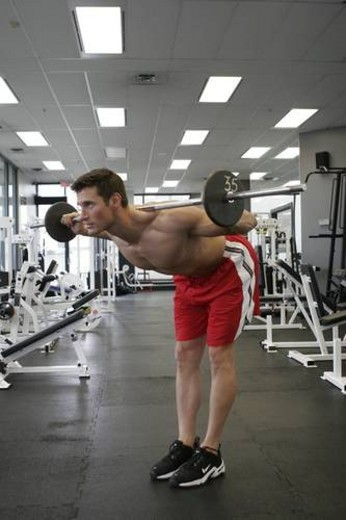 fit male exercising in gym with out a shirt on showing a very ripped muscular body. : Stock Photo