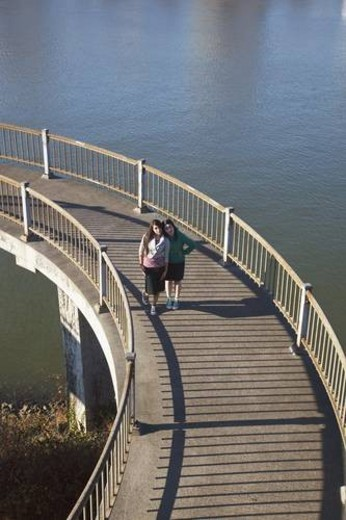 Stock Photo: 4029R-96952 two teenage girls on a pedestrian bridge over a river