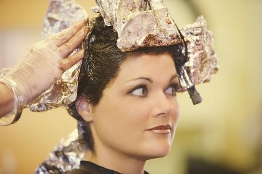 Woman having her hair dyed : Stock Photo