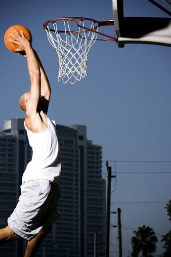 Stock Photo: 4029R-99845 Young  African American man jumping with a basketball on an urban basketball court