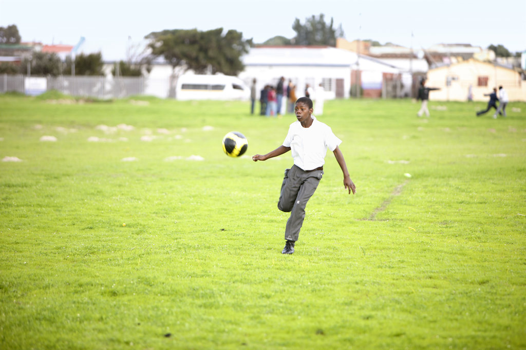 Stock Photo: 4030-4989 School boy kicking Soccer Ball, Cape Town, South Africa
