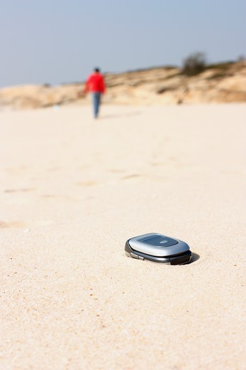 Stock Photo: 4031-148 Mobile phone in the sand with a person walking away, Kinmen County, Taiwan
