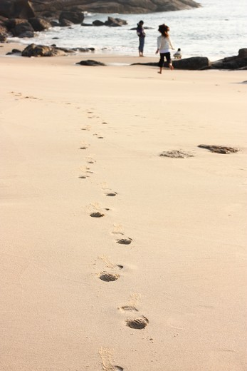 Footprints with a woman and her children in the background on the beach, Kinmen County, Taiwan : Stock Photo