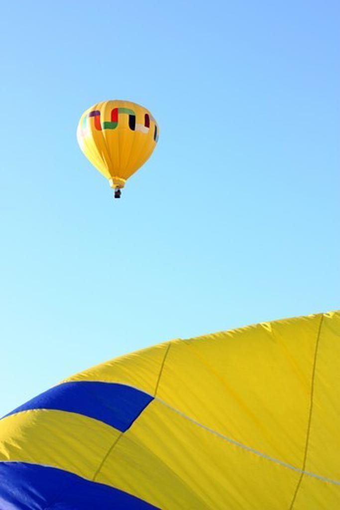 USA, California, Ripon, Hot air balloon flying over inflating balloon at Color the Skies Hot Air Balloon Festival : Stock Photo