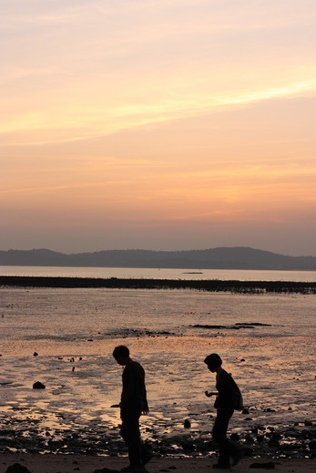 Stock Photo: 4031-421 Taiwan, Kinmen County, Jincheng, Couple walking past oyster beds at sunset