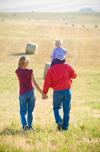 Young couple with their daughter walking in a mowed field, Bozeman, Gallatin County, Montana, USA : Stock Photo