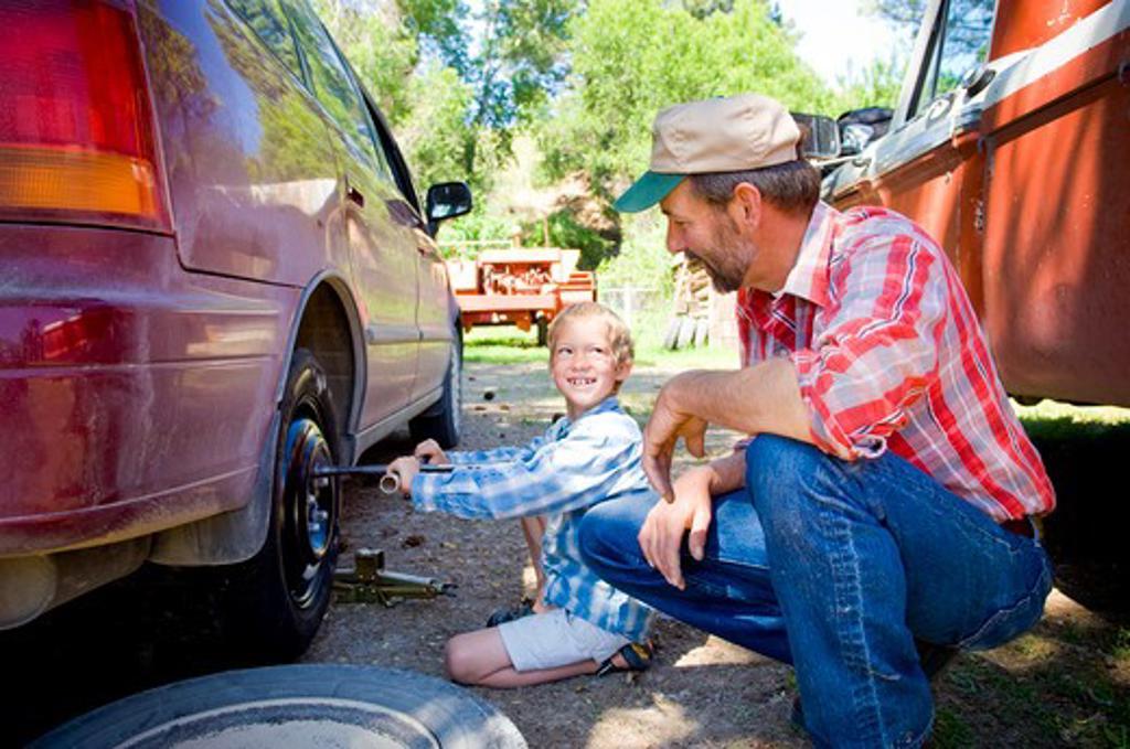 Man watching his son changing the flat tire, Bozeman, Gallatin County, Montana, USA : Stock Photo