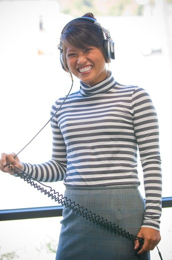Portrait of a young woman listening to headphones, San Diego, California, USA : Stock Photo