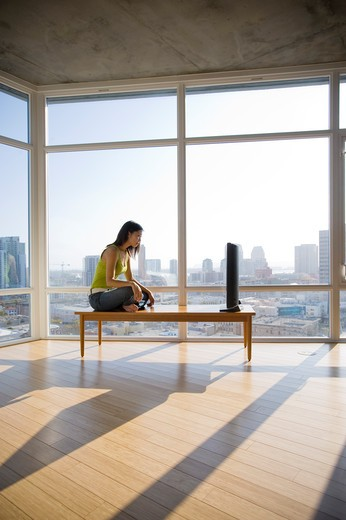 Stock Photo: 4033-249A Young woman watching television in a spacious apartment, San Diego, California, USA