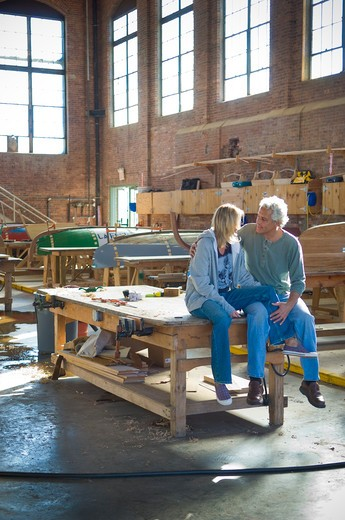 Stock Photo: 4033-258B Mid adult couple romancing in a sailboat workshop, Newport, Rhode Island, USA