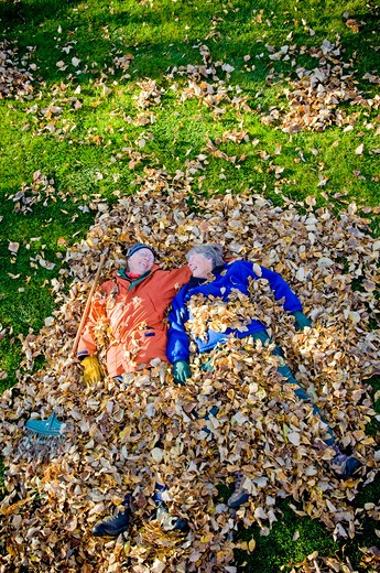 Senior couple lying in heap of leaves, Bozeman, Montana, USA : Stock Photo