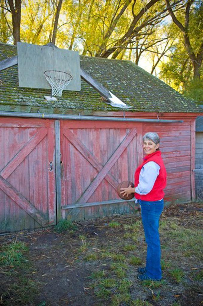 Mature woman holding basketball, Bozeman, Montana, USA : Stock Photo