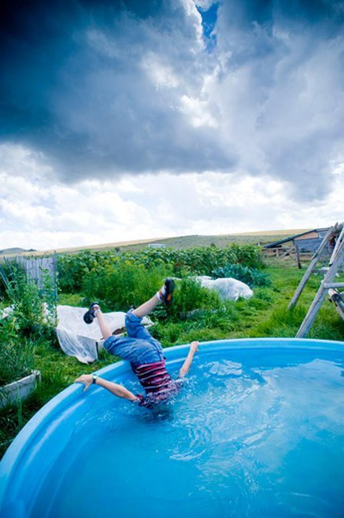 Boy sticking his head in a backyard pool, Bozeman, Montana, USA : Stock Photo