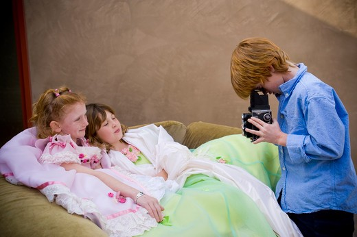 Boy taking a picture of two girls in fancy dresses, San Diego, California, USA : Stock Photo