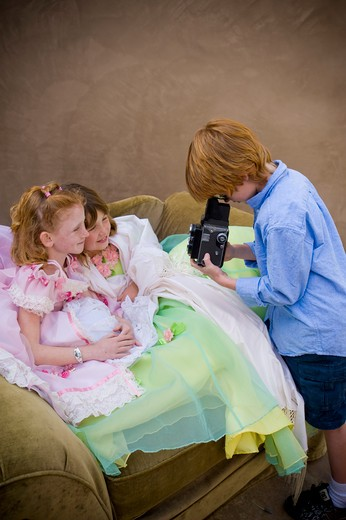 Stock Photo: 4033-388B Boy taking a picture of two girls in fancy dresses, San Diego, California, USA