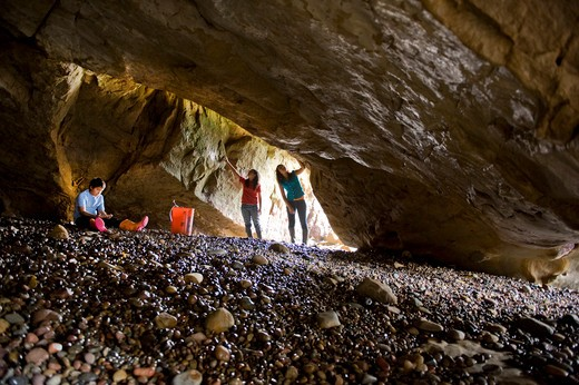 Stock Photo: 4033-393 Three children looking around in a sea cave