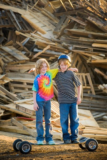 Stock Photo: 4033-395 Two boys standing in front of a heap of recyclable wooden products