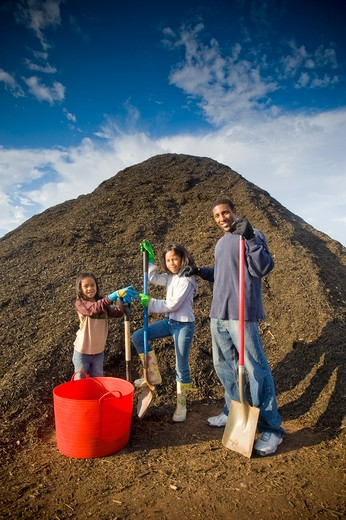 Family in front of a heap of compost : Stock Photo