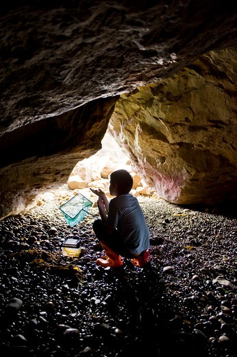 Boy holding a butterfly net in a sea cave : Stock Photo