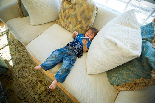 High angle view of a boy listening to mp3 player on a couch : Stock Photo