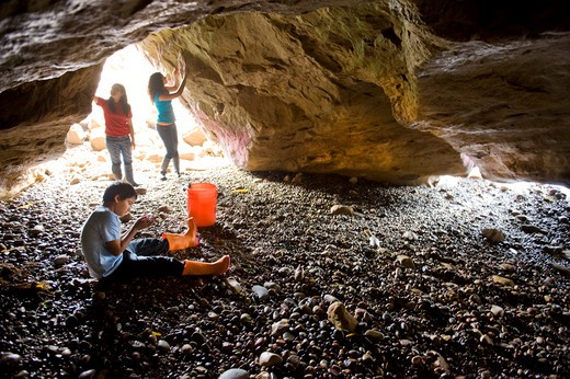 Stock Photo: 4033-407 Three children looking around in a sea cave