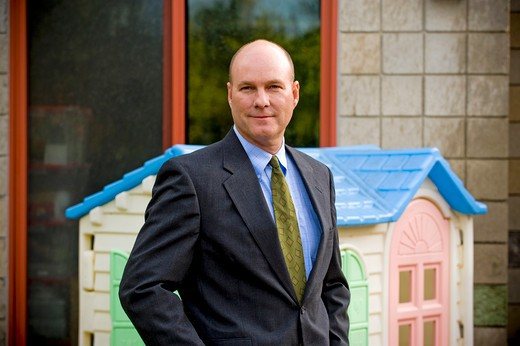 Portrait of a businessman standing in front of a model home : Stock Photo