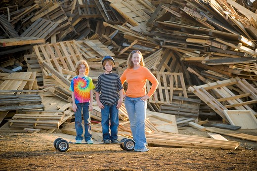 Young woman standing with her children in front of a heap of recyclable wooden products : Stock Photo