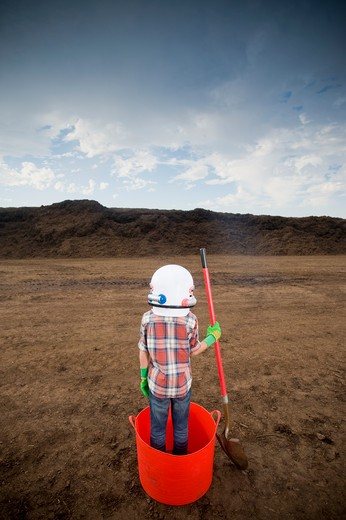 Stock Photo: 4033-417 Boy wearing a space helmet and standing in a bucket at a landfill