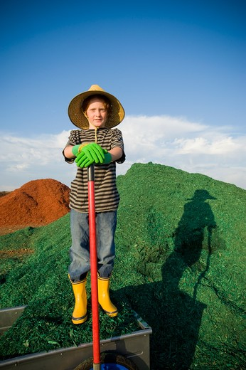 Stock Photo: 4033-420B Boy with a shovel in front of a heap of dyed wood chips