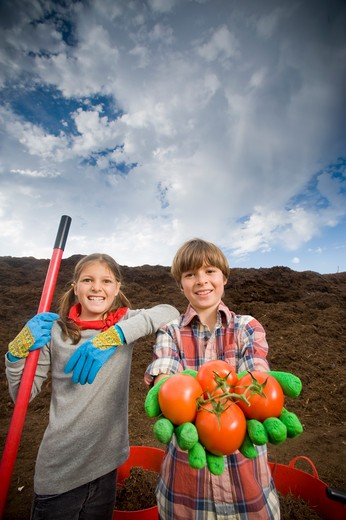Girl standing with a boy holding tomatoes : Stock Photo