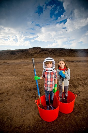 Stock Photo: 4033-427A Boy imitating an astronaut standing with a girl in buckets