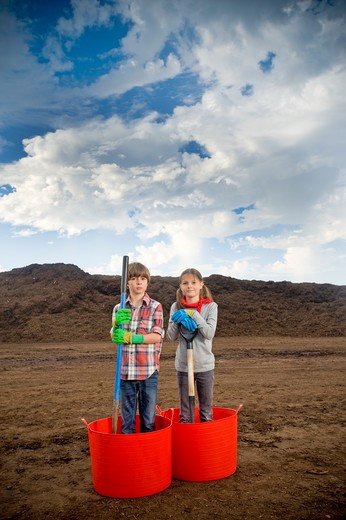 Boy and a girl standing in buckets with a mountain of compost in the background : Stock Photo
