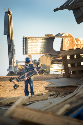 Boy with a skateboard watching heavy machinery at a landfill : Stock Photo