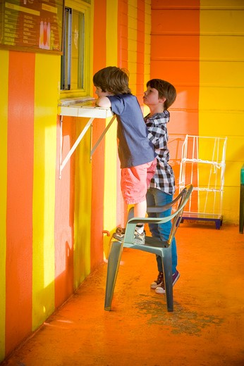 Two boys standing at the order window of a restaurant : Stock Photo