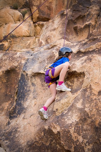 Girl rock climbing, Joshua Tree National Monument, California, USA : Stock Photo