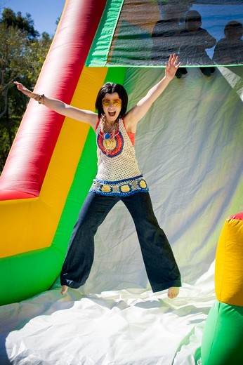 Young woman jumping on an inflatable slide : Stock Photo