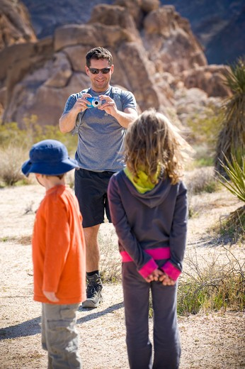 Mid adult man taking a picture of his children, Joshua Tree National Monument, California, USA : Stock Photo
