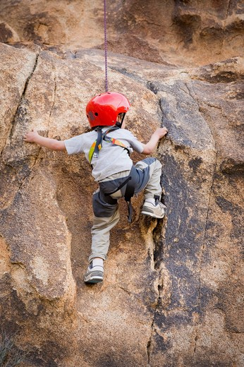 Stock Photo: 4033-451 Boy rock climbing, Joshua Tree National Monument, California, USA