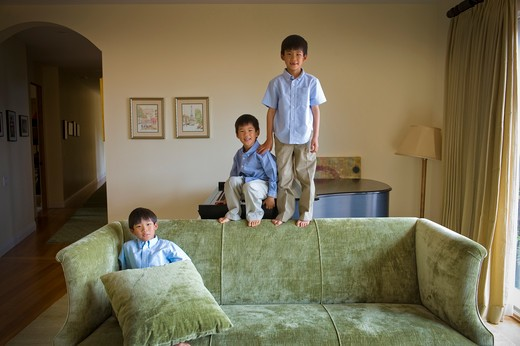 Stock Photo: 4033-453 Three boys playing on a couch