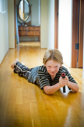 Boy playing with a toy gun : Stock Photo