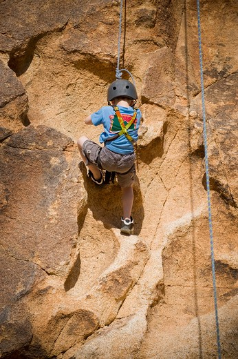 Stock Photo: 4033-461 Boy rock climbing, Joshua Tree National Monument, California, USA