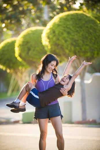 Mid adult woman playing with her daughter in a park : Stock Photo