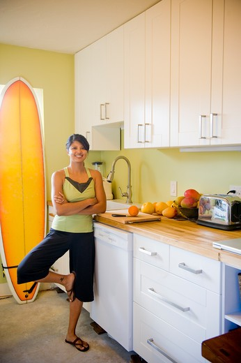 Young woman practicing yoga in kitchen : Stock Photo